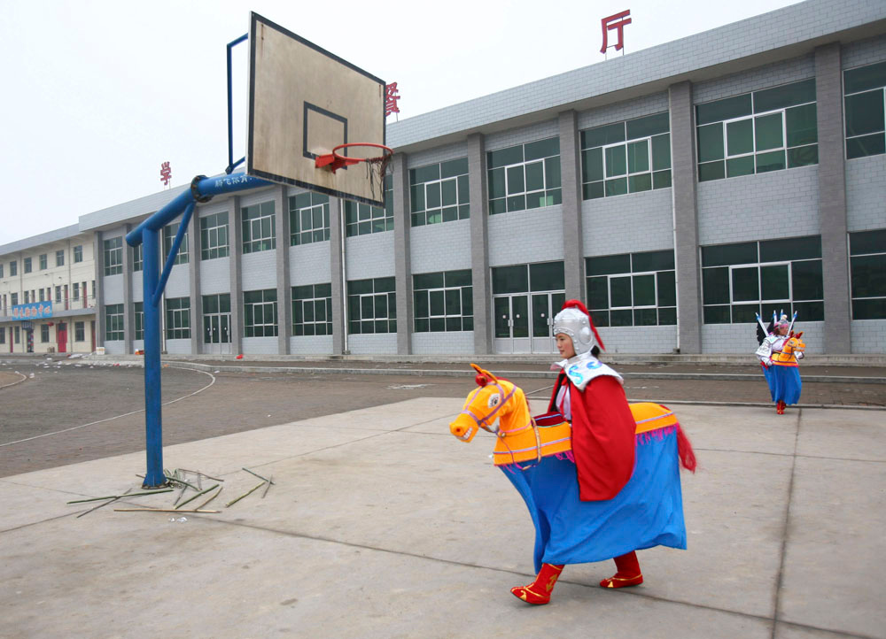 Description of . A rural performer walks across a playground during a performance for the upcoming Chinese Lantern Festival March 2, 2007 in Fuxian County of Shaanxi Province, China. After the Lunar New Year, China will usher the Lantern Festival celebrated on March 4, 2007, the fifteenth day of the first lunar month.  (Photo by China Photos/Getty Images)