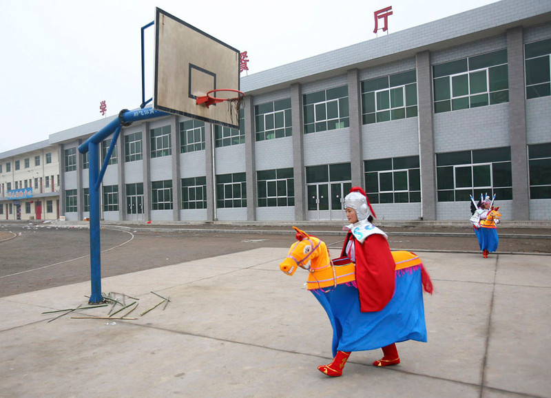 . A rural performer walks across a playground during a performance for the upcoming Chinese Lantern Festival March 2, 2007 in Fuxian County of Shaanxi Province, China. After the Lunar New Year, China will usher the Lantern Festival celebrated on March 4, 2007, the fifteenth day of the first lunar month.  (Photo by China Photos/Getty Images)