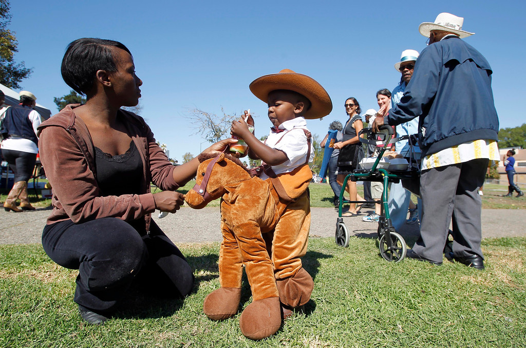 . Dominic Hampton, 2, and his mom Amyra, left, of Oakland, share an ice during the 39th annual Oakland Black Cowboy Parade and Heritage Festival at De Fremery Park in Oakland, Calif., on Saturday, Oct. 5, 2013. The event also featured food, entertainment and pony rides for kids. The Oakland Black Cowboy Association began in 1975 and educates the public about the role that black cowboys played in history and building of the west. (Jane Tyska//Bay Area News Group)