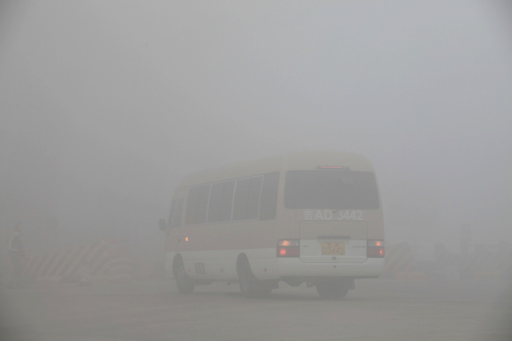 . A bus is seen at a toll booth on a highway as vehicles are forced to wait due to heavy smog in Jilin, northeast China\'s Jilin province on October 22, 2013.    AFP PHOTOSTR/AFP/Getty Images
