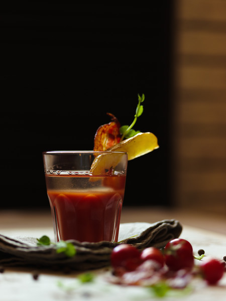 A glass of Bloody Mary with piece of bacon and potato on a top of a glass on a blurred background. A heap of organic cherry tomatoes, spicy peppercorns and green herbs on a white tablecloth.