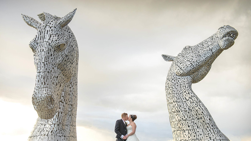 Wedding Photography of Nina & Scott, Kelpies Scupltures in Falkirk, Photography is of the Bride & Groom standing kissing in front of The Kelpies Sculptures