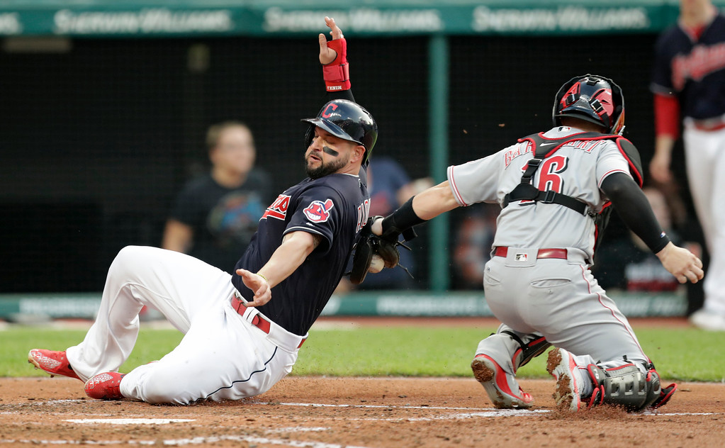 . Cleveland Indians\' Yonder Alonso, left, slides safely into home plate as Cincinnati Reds catcher Tucker Barnhart can\'t make the tag during the third inning of a baseball game Wednesday, July 11, 2018, in Cleveland. (AP Photo/Tony Dejak)