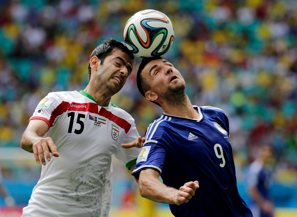. Iran\'s Pejman Montazeri, left, and Bosnia\'s Vedad Ibisevic battle for the ball during a group F World Cup soccer match between Bosnia and Iran at the Arena Fonte Nova in Salvador, Brazil, Wednesday, June 25, 2014. (AP Photo/Fernando Llano)