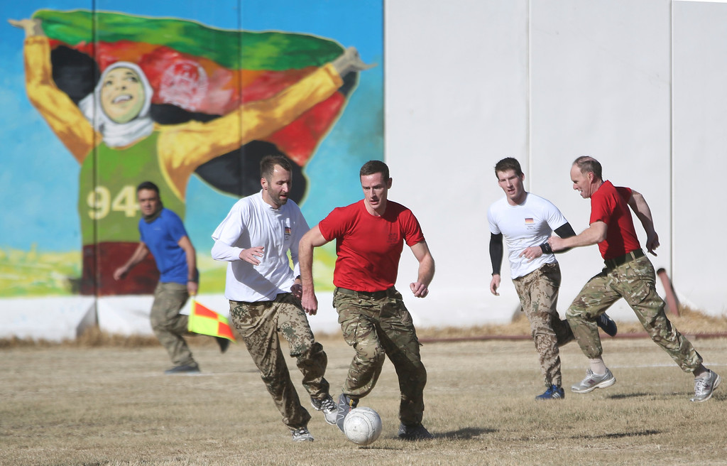 . British soldiers, in red, and German soldiers, in white, battle for the ball during a soccer match in Christmas day in Resolute Support HQ, in Kabul, Afghanistan, Sunday, Dec. 25, 2016. NATO soldiers, Resolute Support mission played a soccer match marking the 102 years anniversary of WW1 in Kabul. The match ended up with British winning the match by (1-0). (AP Photos/Massoud Hossaini)