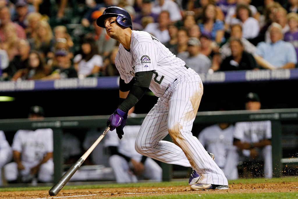 . Colorado Rockies shortstop Troy Tulowitzki hits a single during the fourth inning of a baseball game against the Cincinnati Reds, Friday, Aug. 30, 2013, in Denver. (AP Photo/Barry Gutierrez)