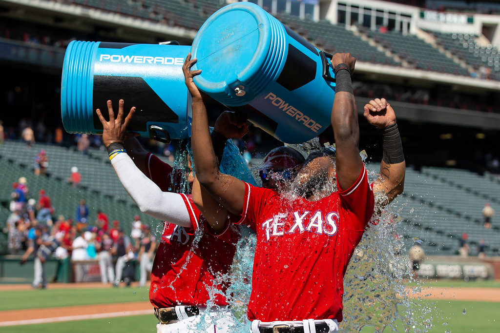 . Texas Rangers\' Elvis Andrus (L) and Texas Rangers\' Jurickson Profar (R) douse themselves and Texas Rangers\' Rougned Odor (C) with a sports drink after a baseball game against the Cleveland Indians, Sunday, July 22, 2018, in Arlington, Texas. The Rangers won 5-0. (AP Photo/Sam Hodde)
