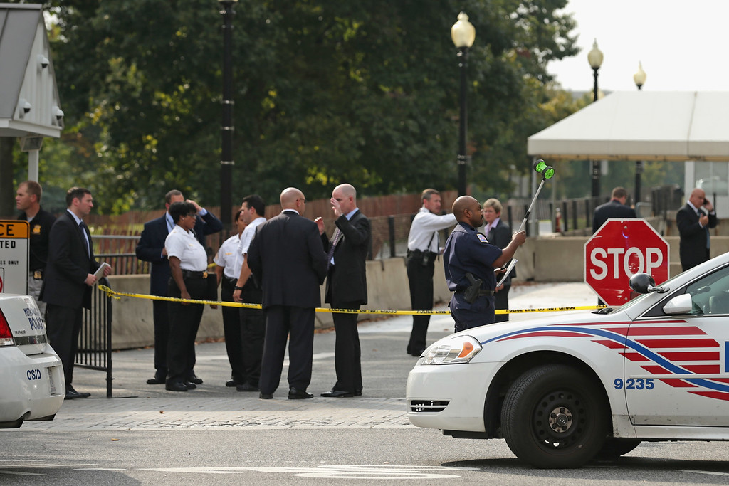 . U.S. Secret Service Uniform Division officers and Metropolitan Police Department officers investigate a vehicle security barrier outside the White House October 3, 2013 in Washington, DC. Two people were injured after a car chase began at this barrier and ended near the U.S. Capitol with gun shots fired.  (Photo by Chip Somodevilla/Getty Images)