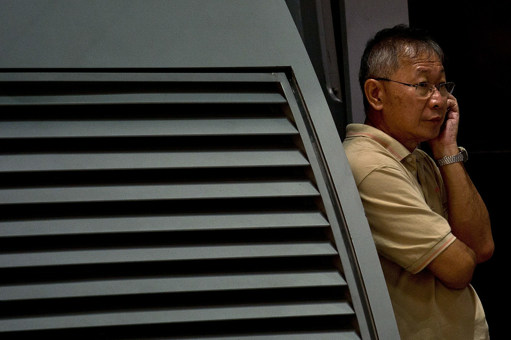 """. A relative of passengers onboard Malaysia Airlines flight MH17 from Amsterdam speaks on the phone as he waits for information outside the family holding area at the Kuala Lumpur International Airport in Sepang on July 18, 2014. Malaysia Airlines said on July 17 that it had \""""lost contact\"""" with one of its passenger planes carrying 295 people over eastern Ukraine, amid speculation it had been shot down. Pro-Russian rebels fighting central Kiev authorities claimed that the Malaysian airline that crashed in Ukraine had been shot down by a Ukrainian jet. The head of Ukraine\'s air traffic control agency said Thursday that the crew of the Malaysia Airlines jet that crashed in the separatist east had reported no problems during flight.   AFP PHOTO/ MANAN  VATSYAYANA/AFP/Getty Images"""