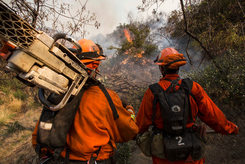 . A fire crew works on a fire line as a wildfire burns just north of the San Gabriel Valley community of Glendora, Calif., on Thursday, Jan 16, 2014. Southern California authorities have ordered the evacuation of homes at the edge of a fast-moving wildfire burning in the dangerously dry foothills of the San Gabriel Mountains. (AP Photo/Ringo H.W. Chiu)