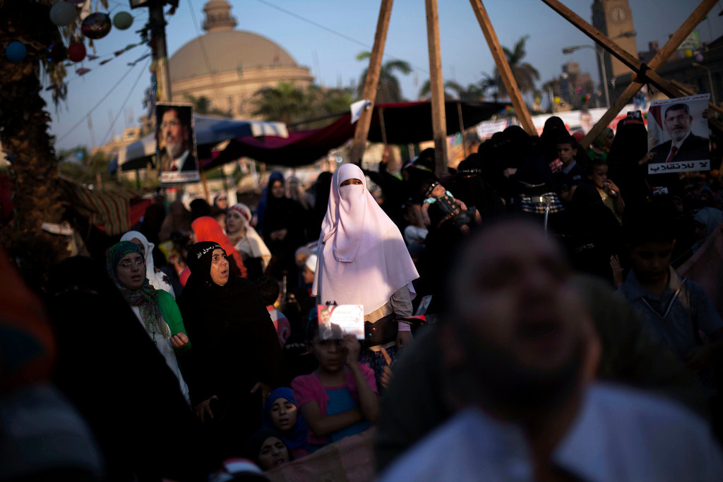 """. An Egyptian woman, a supporter of Egypt\'s ousted President Mohammed, is seen before the morning pray during the celebration of the \""""Eid al-Fitr\"""" holiday (end of Ramadan) near Cairo University in Giza, Egypt, Thursday, Aug. 8, 2013. This year\'s holiday is overshadowed by the deep divisions in Egypt, with the interim government planning to celebrate the feast with outdoor prayers and protests in town center squares and Morsi\'s supporters marking the holiday with their own protests and prayers, including at the two major sit-ins by the Islamists in Cairo. (AP Photo/Manu Brabo)"""