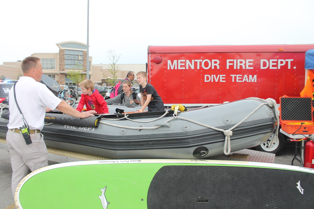 . Kristi Garabrandt � The News-Herald <br> Justin Dopp, 6 and his brother Caleb, 3,  sit in the Mentor Fire Department\'s Dive Team rescue boat while their mother Robin and Dive Team commander Mike Ulrich look on during the 36th Annual Heroes Day held at Great Lakes Mall, May 12, 2018.