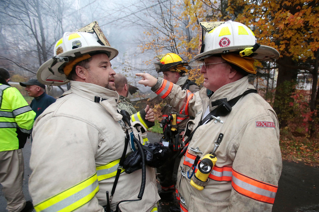 . Lanesborough Fire Chief Charlie Durffe, left, and Pittsfield Fire Chief Robert Czerwinski discuss a fire that leveled a house on National Street in Lanesborough. The house was insulated with foam, making the blaze burn fast. Thursday, October 31, 2013.  (Stephanie Zollshan | Berkshire Eagle Staff)