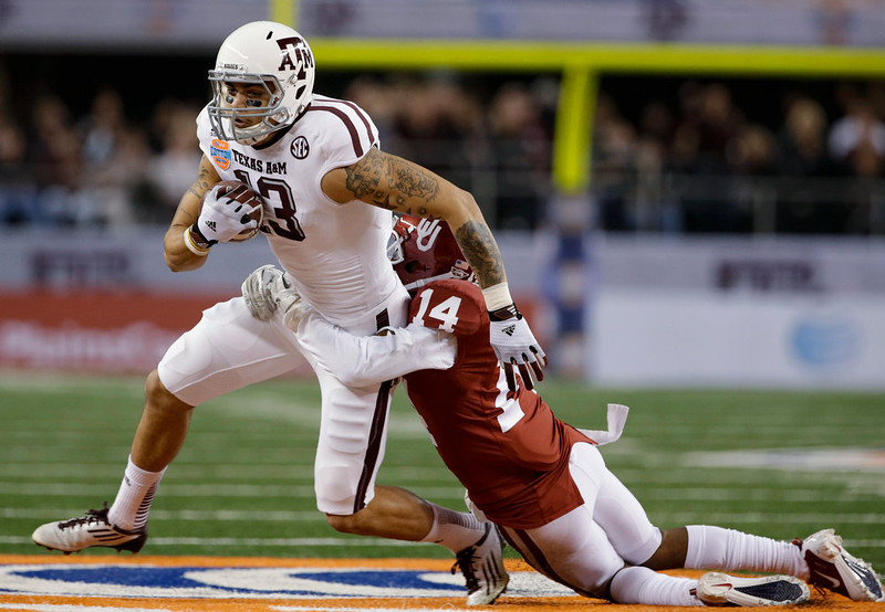 . Oklahoma\'s Durron Neal (13) drags Oklahoma  defensive back Aaron Colvin (14) along after making a reception in the first half of the Cotton Bowl NCAA college football game Friday, Jan. 4, 2013, in Arlington, Texas. (AP Photo/Tony Gutierrez)