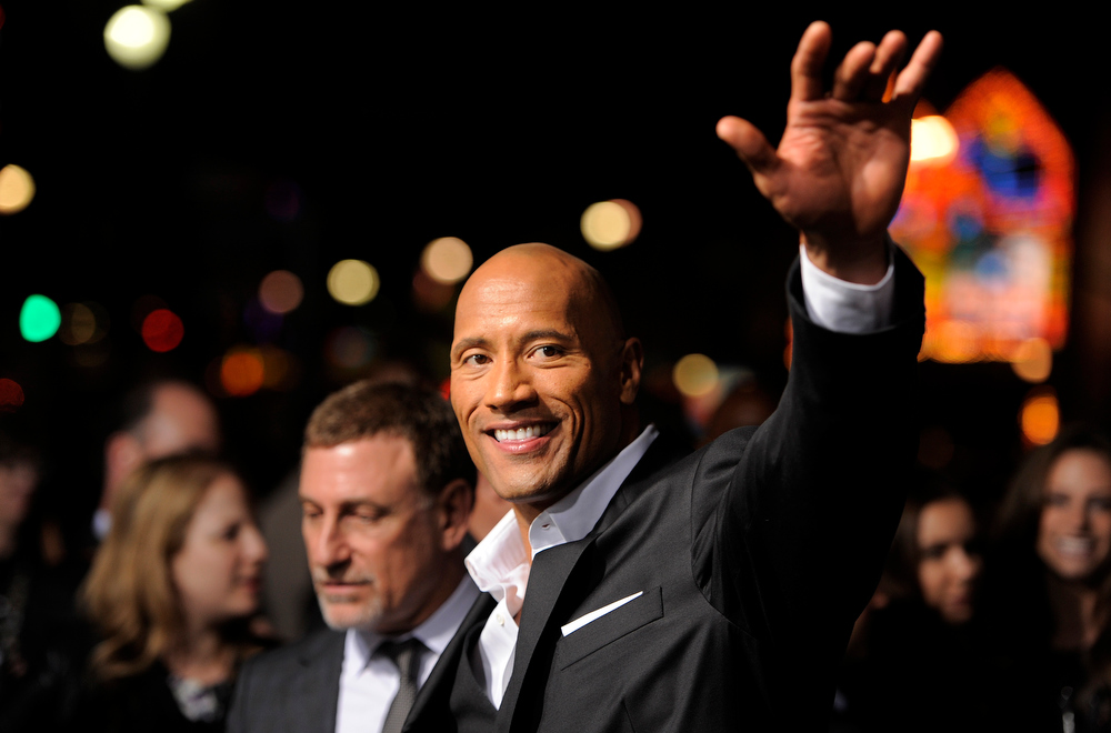 ". Dwayne Johnson, a cast member in ""G.I. Joe: Retaliation,\"" waves to fans at the Los Angeles premiere of the film at the TCL Chinese Theatre on Thursday, March 28, 2013 in Los Angeles. (Photo by Chris Pizzello/Invision/AP)"