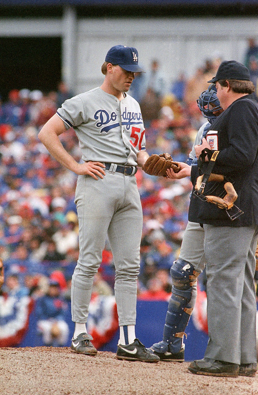 . Home plate umpire Joe West, right, takes the glove of Los Angeles Dodgers pitcher Jay Howell in the eighth inning of Saturday\'s playoff game, Oct. 8, 1988, New York. West ejected Howell after a possible illegal substance was found Howell\'s glove. (AP Photo/Ron Frehm)