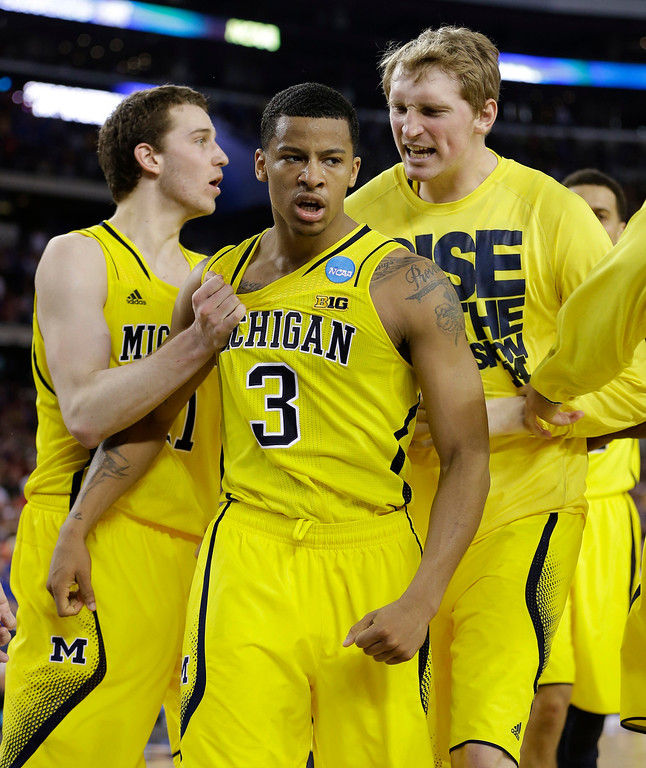 . Michigan\'s Trey Burke (3) is congratulated by teammates after making a three-point basket in the final seconds of the second half of a regional semifinal game against Kansas in the NCAA college basketball tournament, Friday, March 29, 2013, in Arlington, Texas. (AP Photo/David J. Phillip)