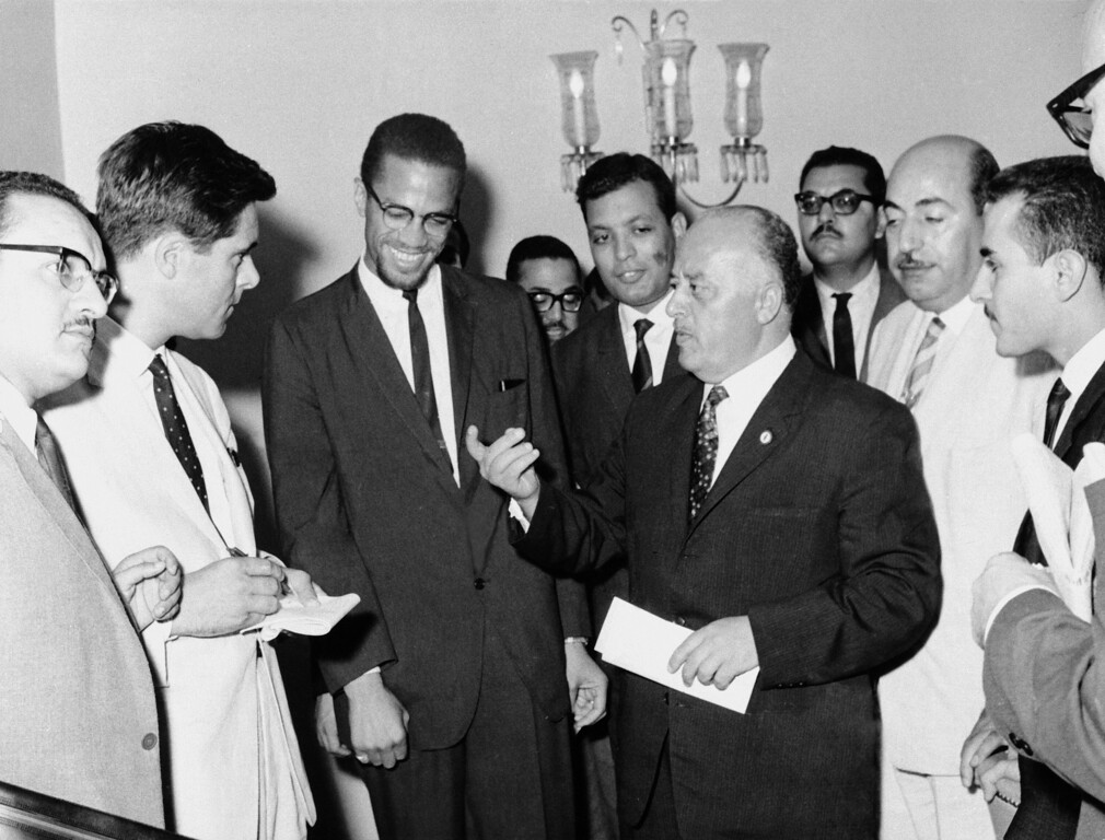 . Malcolm X, left, African-American black muslim leader, third from left, is shown with Ahmed Shukairi, center with extended hand, haed of the newly formed Palestinain organziation, explains at a news conference the significans of each of the four colors on the Palestinian flag in Egypt in Sept. 1964.   (AP Photo)