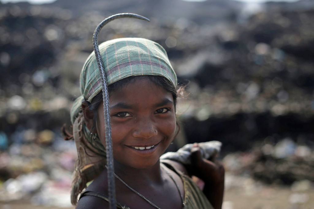 . A ragpicker girl Zahanara Khatun, 12,  looks at the camera as she searches for recyclable items at a garbage dump on Earth Day, on the outskirts of Gauhati, India, Tuesday, April 22, 2014. (AP Photo/Anupam Nath)