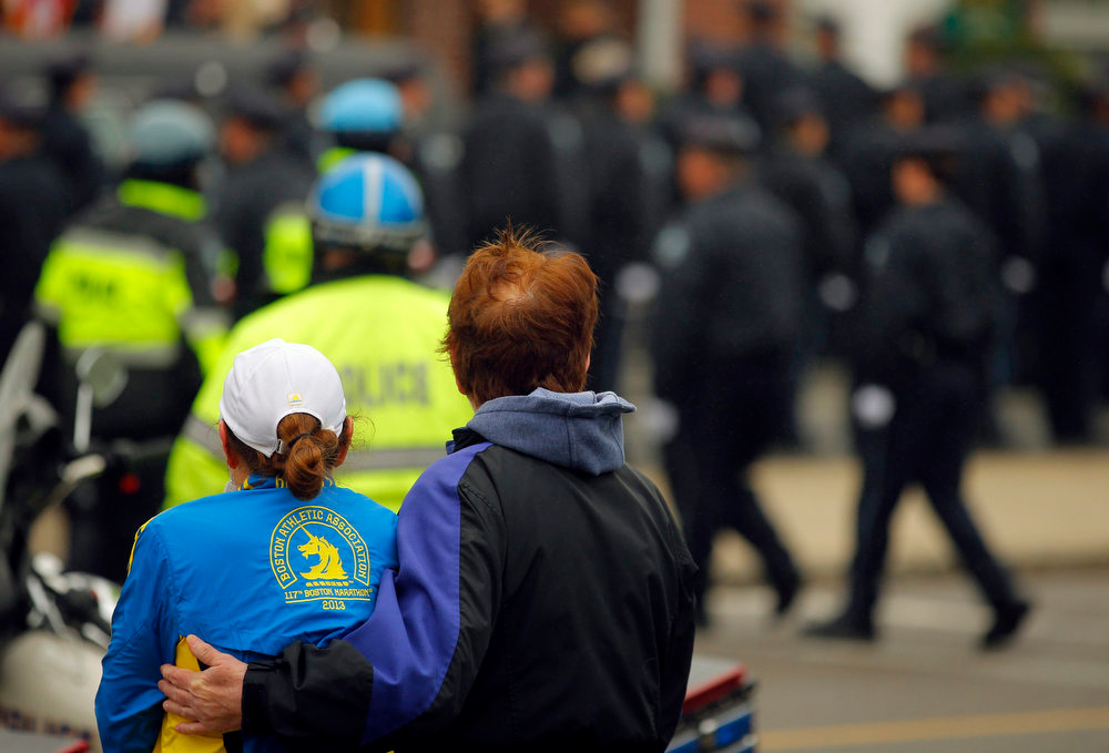 . A woman wearing a Boston Marathon runner\'s jacket watches as police officers file into St. Patrick\'s Church for the funeral of Massachusetts Institute of Technology (MIT) police officer Sean Collier in Stoneham, Massachusetts April 23, 2013. Officer Collier was allegedly killed by the brothers accused of the Boston Marathon bombings, Dzhokhar and Tamerlan Tsarnaev. Two explosions hit the Boston Marathon April 15, killing at least three people and injuring over 100 others.      REUTERS/Brian Snyder