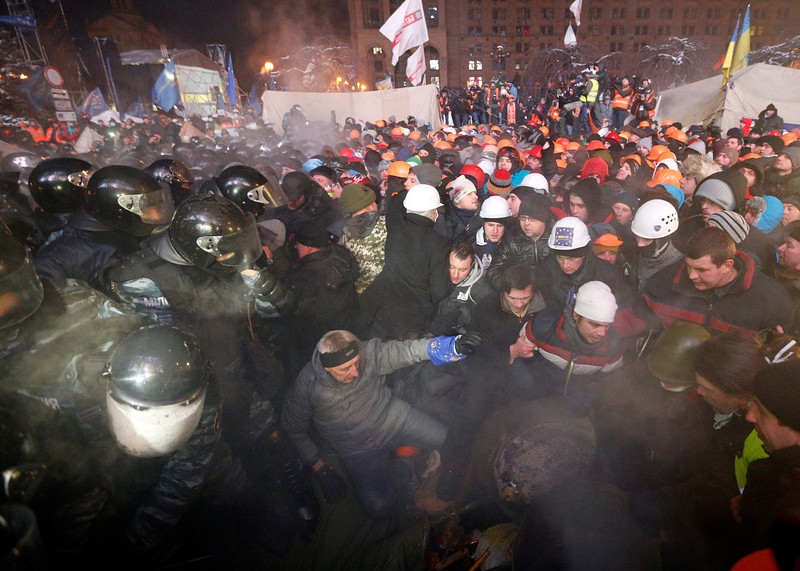 . Pro-EU protesters face off with riot police as they defend a barricade at Independence Square in Kiev, Ukraine, 11 December 2013. Ukrainian riot police reoccupied part of the square where thousands of pro-European protesters demand early elections and resist calls from police to vacate the central Independence Square.  EPA/SERGEY DOLZHENKO