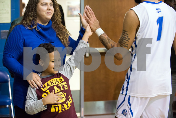 11/30/17 Wesley Bunnell | Staff CCSU Men's Basketball defeated North Carolina A&T on Thursday evening at Derrick Gymnasium in New Britain. Jonathan Ruiz, age 9, gets a high five from Tyler Kohl (1) as he stands with his aunt Inez Bonilla.