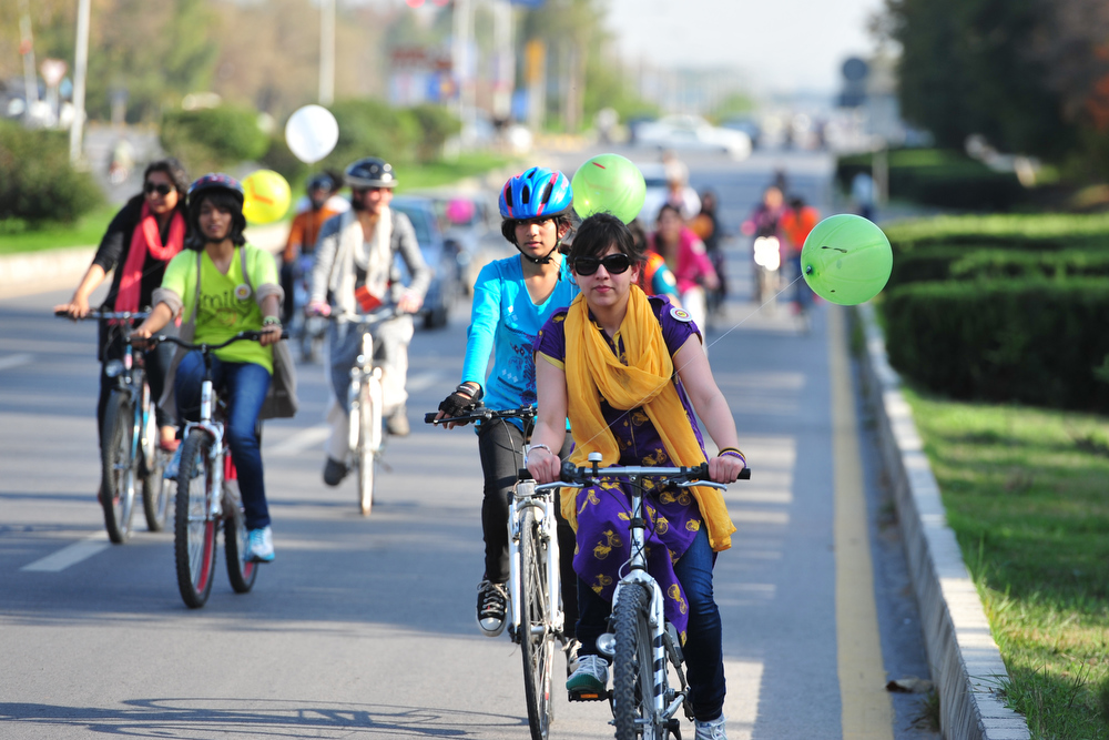 . Pakistani women ride their bikes towards the city\'s landmark Faisal Mosque to mark International Women\'s day in Islamabad on March 8, 2013.  A group of determined women took to bikes March 8, riding through the Pakistani capital to highlight their rights and love of exercise in a culture that often treats them as second-class citizens.   FAROOQ NAEEM/AFP/Getty Images