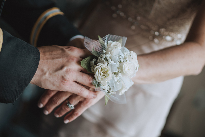 Groom placing flower corsage on his mothers wrist.