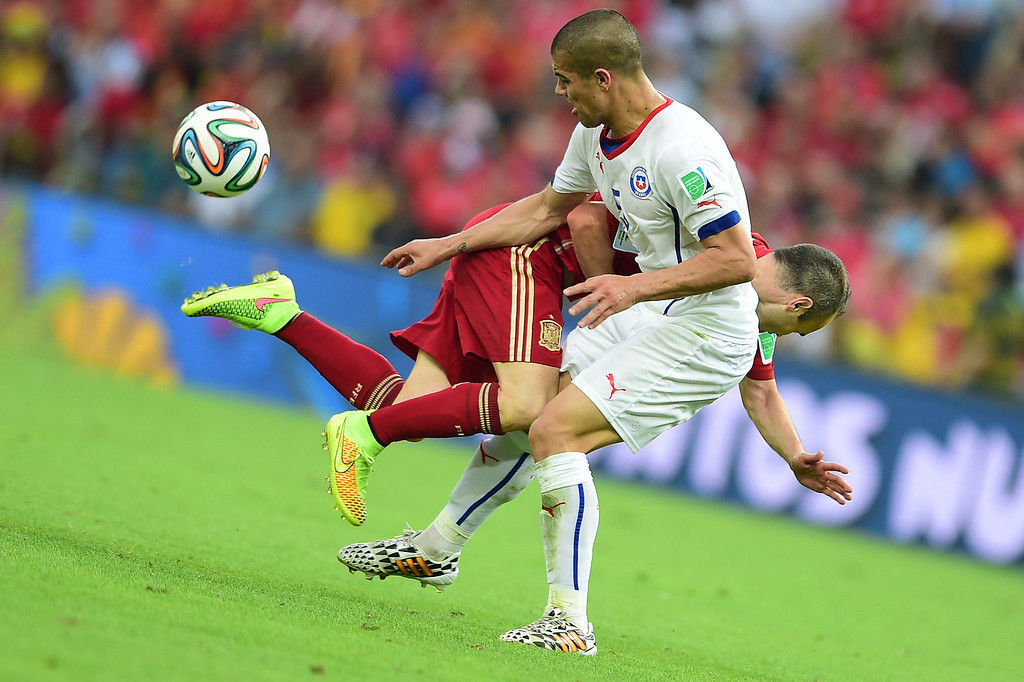 . Spain\'s midfielder Andres Iniesta (L) falls to the ground as Chile\'s midfielder Francisco Silva vies for the ball a Group B football match between Spain and Chile in the Maracana Stadium in Rio de Janeiro during the 2014 FIFA World Cup on June 18, 2014.  MARTIN BERNETTI/AFP/Getty Images