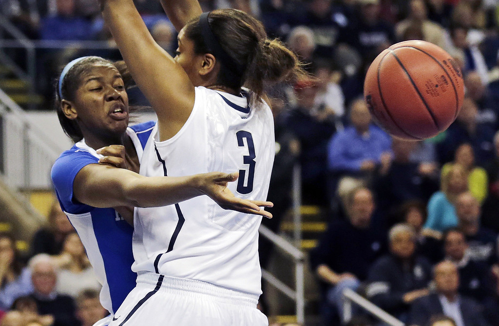 . Kentucky center DeNesha Stallworth, left, dumps off the ball as she is pressured by Connecticut forward Morgan Tuck (3) in the first half of a women\'s NCAA regional final basketball game in Bridgeport, Conn., Monday, April 1, 2013. (AP Photo/Charles Krupa)
