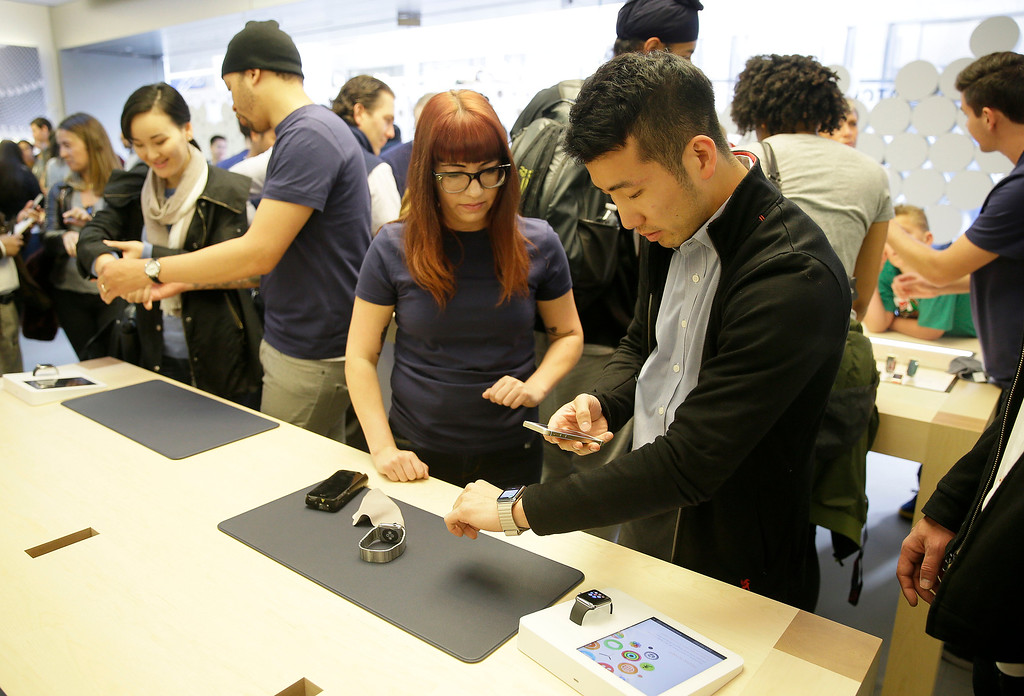 . An Apple store worker, center left, helps a  customer try on Apple\'s new watch in San Francisco, Friday, April 10, 2015. Apple has started taking orders for the watch on its website and the Apple Store app. Currently, that\'s the only way Apple is selling the watch, with shipments scheduled to start April 24. (AP Photo/Eric Risberg)