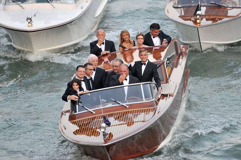 . George Clooney, waves from a boat prior his marriage with Amal Alamuddin  in Venice, Italy, Saturday, Sept. 27, 2014. (AP Photo/Luigi Costantini)