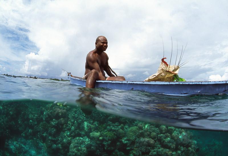 Papuaner mit seinem Einbaum