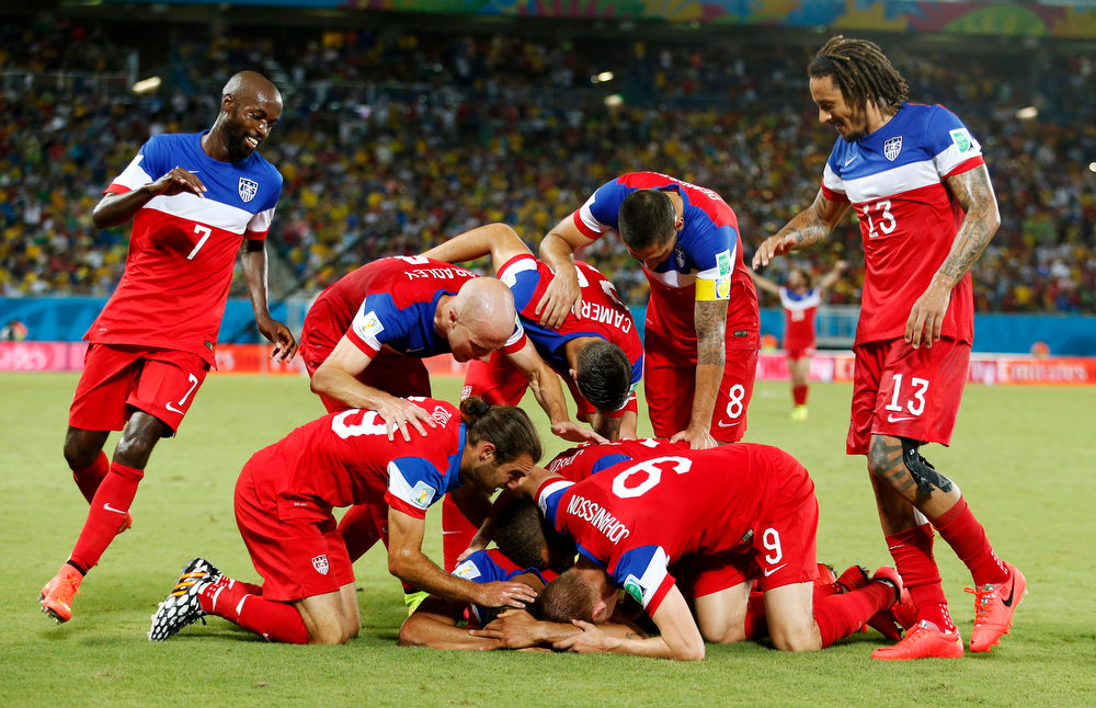 Description of . The United States team surrounds John Brooks after he scored his side's second goal to defeat Ghana 2-1 during the group G World Cup soccer match between Ghana and the United States at the Arena das Dunas in Natal, Brazil, Monday, June 16, 2014. (AP Photo/Julio Cortez)