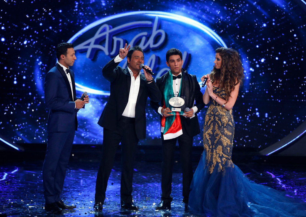 ". Palestinian singer Mohammed Assaf (2nd R) stands next to Lebanese singer Assi al-Hilani (2nd L) after Assaf was announced the winner during the Season 2 finale of ""Arab Idol\"" in Zouk Mosbeh area, north of Beirut June 22, 2013. REUTERS/Mohammed Azakir"