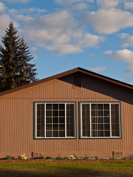 Pretty day, mundane scene. In the eighties there was a building boom in Alaska, and many of the houses in the Mendenhall Valley in Juneau were built then, most somewhat small and simple, with plywood siding. These are far from 1920's craftsmen homes, but people make the best of them and still keep them up.