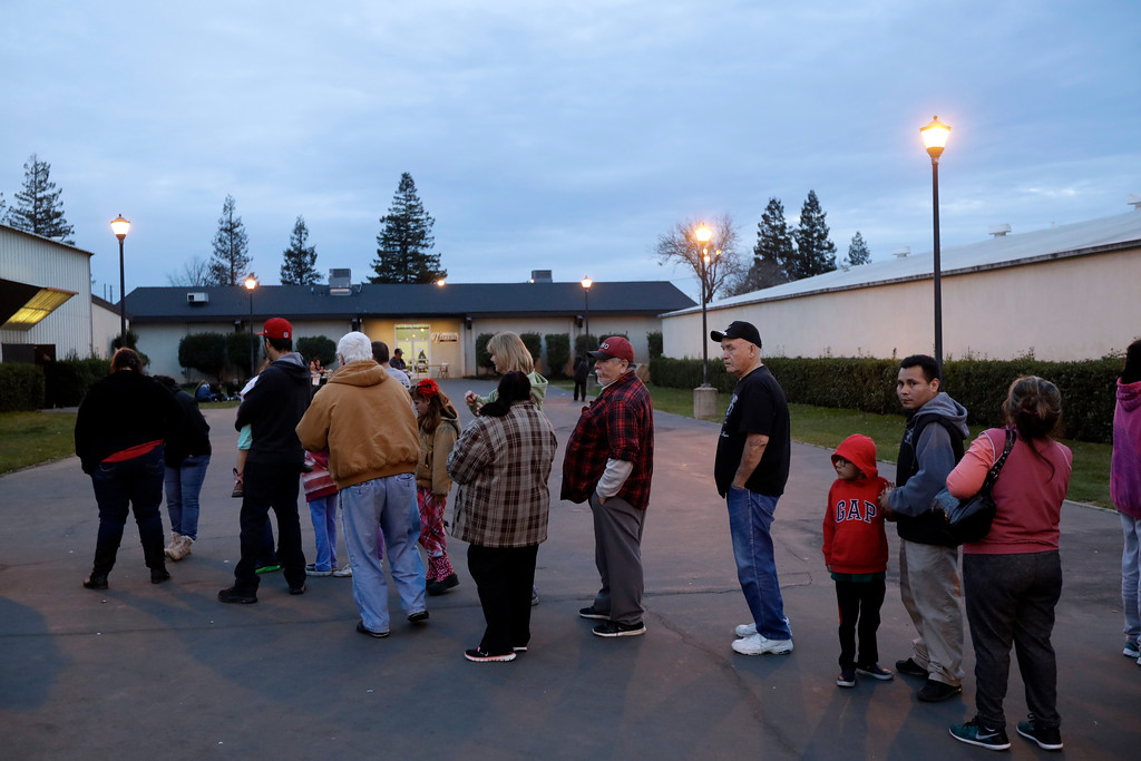. People line up for a meal at a shelter for evacuees from cities surrounding the Oroville Dam, Monday, Feb. 13, 2017, in Chico, Calif. The thousands of people who were ordered to leave their homes after a damaged California spillway threatened to unleash a 30-foot wall of water may not be able to return until significant erosion is repaired, authorities said Monday. (AP Photo/Marcio Jose Sanchez)