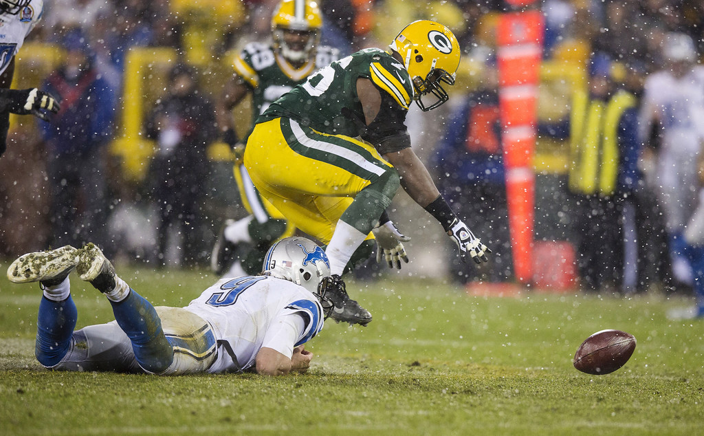 . GREEN BAY, WI - DECEMBER 9:  Matthew Stafford #9 of the Detroit Lions can not get a hold on the ball he fumbled as Mike Daniels #76 of the Green Bay Packers scoops it up at Lambeau Field on December 9, 2012 in Green Bay, Wisconsin.  (Photo by Tom Lynn/Getty Images)