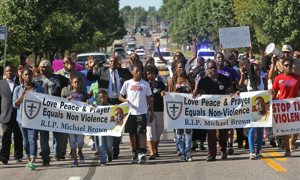 . A march organized by area ministers makes its way down W. Florissant in Ferguson, Mo. on Wednesday, Aug. 13, 2014. On Saturday, Aug. 9, 2014, a white police officer fatally shot Michael Brown, an unarmed black teenager, in the St. Louis suburb. (AP Photo/St. Louis Post-Dispatch, J.B. Forbes)