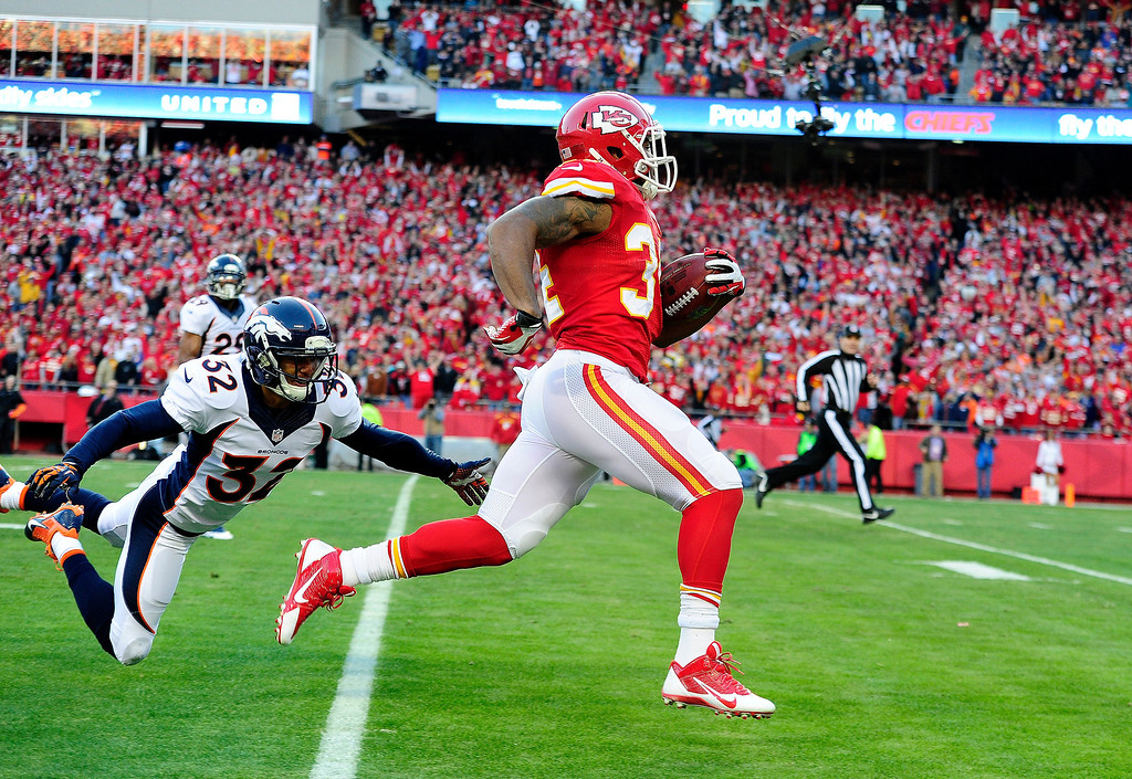 . Tony Carter (32) of the Denver Broncos cannot stop Knile Davis (34) of the Kansas City Chiefs from taking a kickoff to the house during the first half of action at Arrowhead Stadium.  (Photo by AAron Ontiveroz/The Denver Post)