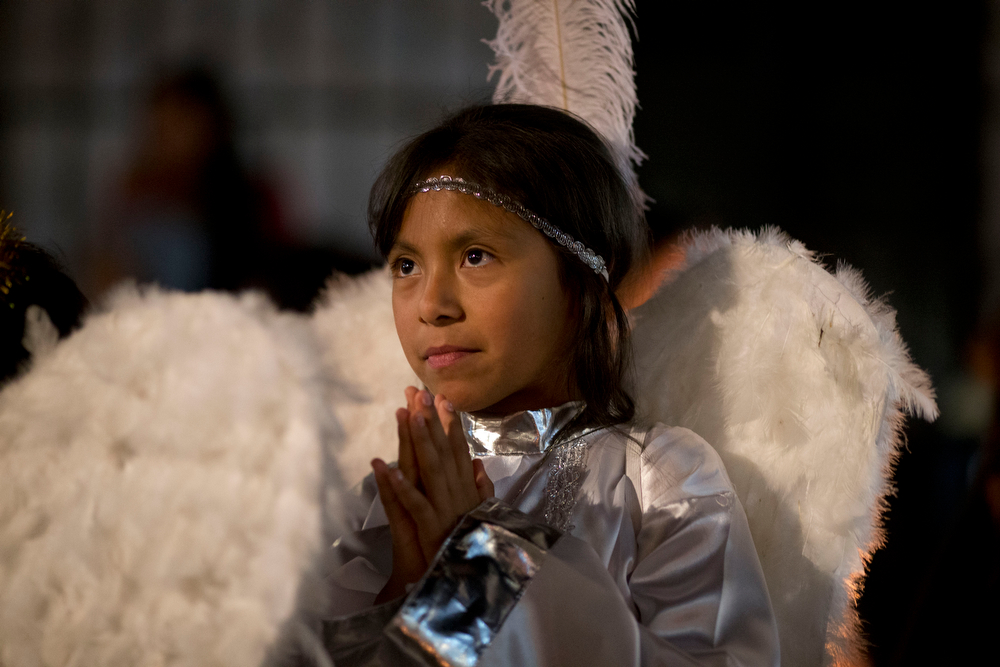 . A girl dressed as an angel walks in a Holy Week procession in Taxco, Mexico, in the early hours of Friday, April 18, 2014. Holy Week commemorates the last week of the earthly life of Jesus Christ, culminating in his crucifixion on Good Friday and his resurrection on Easter Sunday. (AP Photo/Rebecca Blackwell)
