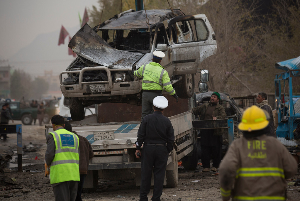 . Afghan policemen remove a damaged car after a powerful suicide vehicle bomb tore through the outskirts of Kabul,  Afghanistan, Saturday, Nov. 16, 2013.  (AP Photo/Anja Niedringhaus)