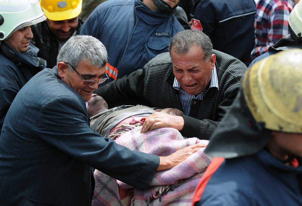 . A man cries over the body of a miner being carried outside the coal mine in Soma, Turkey, Wednesday, May 14, 2014. (AP Photo/Depo Photos)