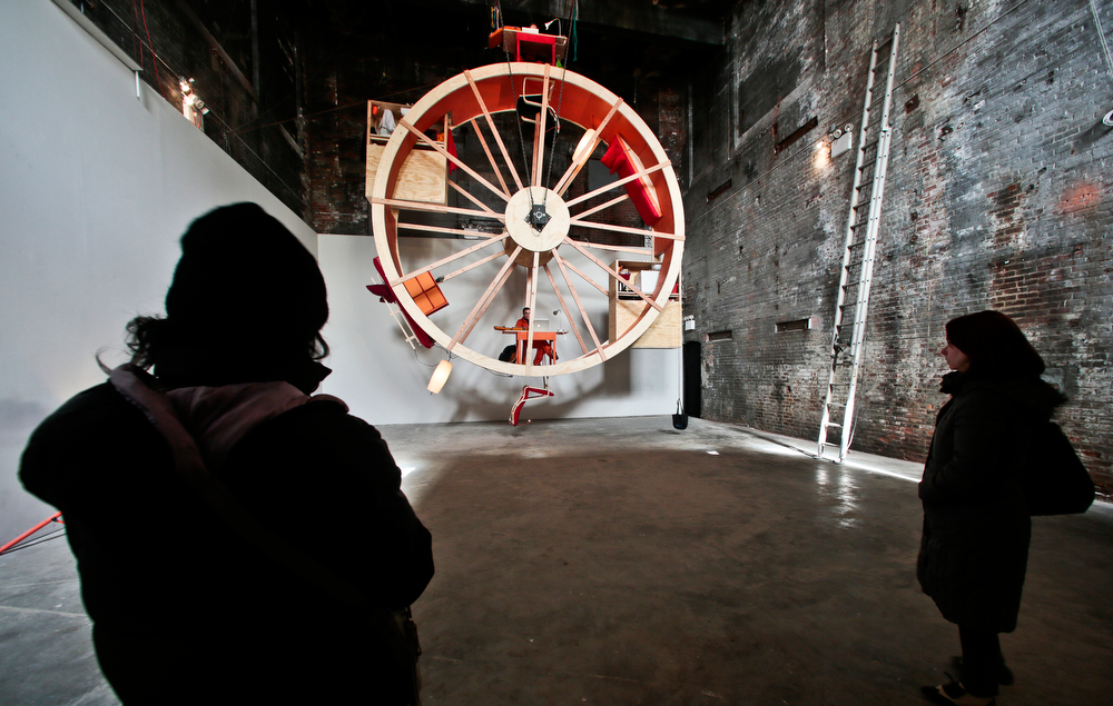 """. Visitors view the performance art \""""In Orbit,\"""" a 25-foot wheel made from wood, steel, and furniture, which is home for artists Ward Shelley, top, and Alex Schweder, bottom, for 10 days at the Boiler gallery in the Brooklyn borough of New York, Tuesday, March 4, 2014. They will share two living units arrayed over the hamster-wheel-like sculpture, with Shelly living on the outside and Schweder on the inside. The structure will remain on view through April 5.  (AP Photo/Bebeto Matthews)"""