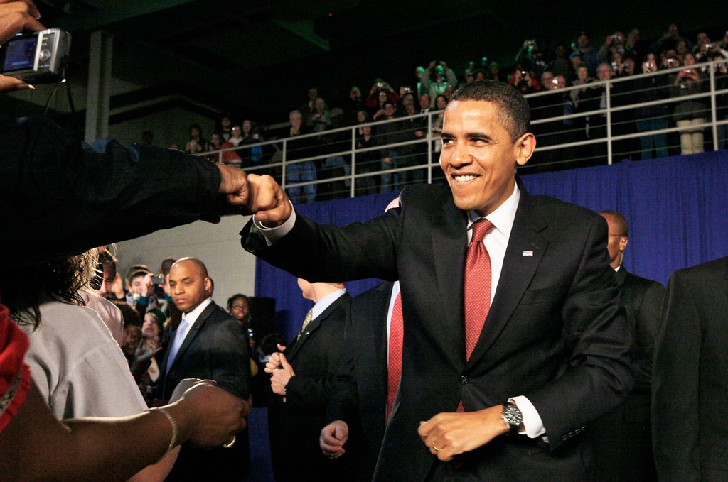 . President Barack Obama bumps fists with an audience member as he arrives for a town hall style meeting to discuss his economic stimulus package, Monday, Feb. 9, 2009, at Concord Community High School in Elkhart, Ind. (AP Photo/Charles Dharapak)