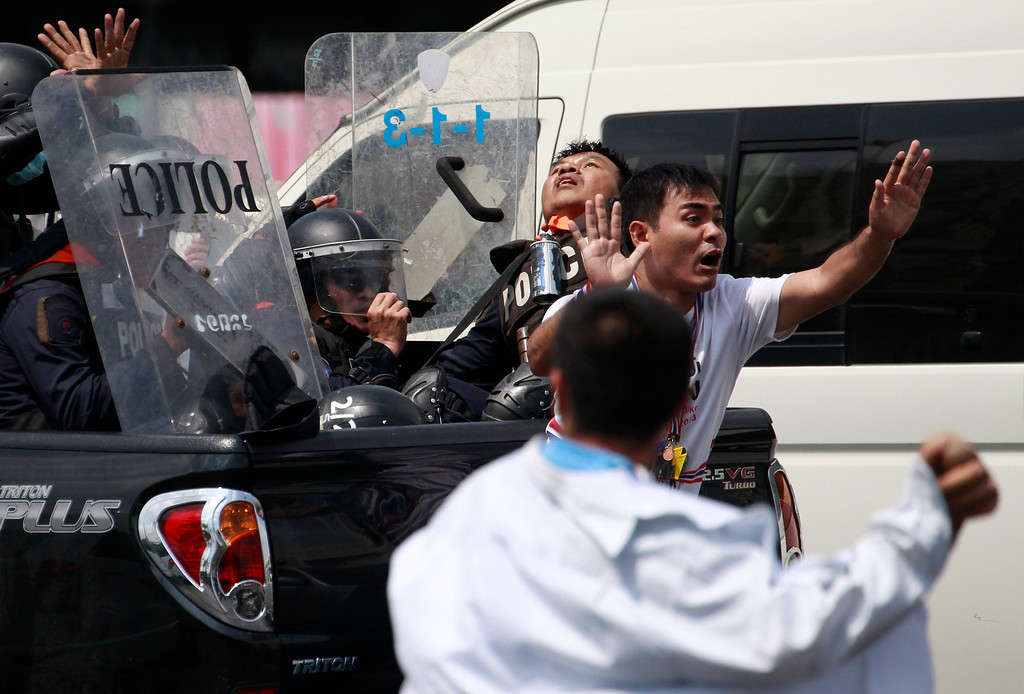 . A protester, right, tries to stop colleagues from attacking policemen retreating on a pick up truck during a clash between police force and anti-government protesters Tuesday, Feb. 18, 2014 in Bangkok, Thailand. (AP Photo/Wason Wanichakorn)