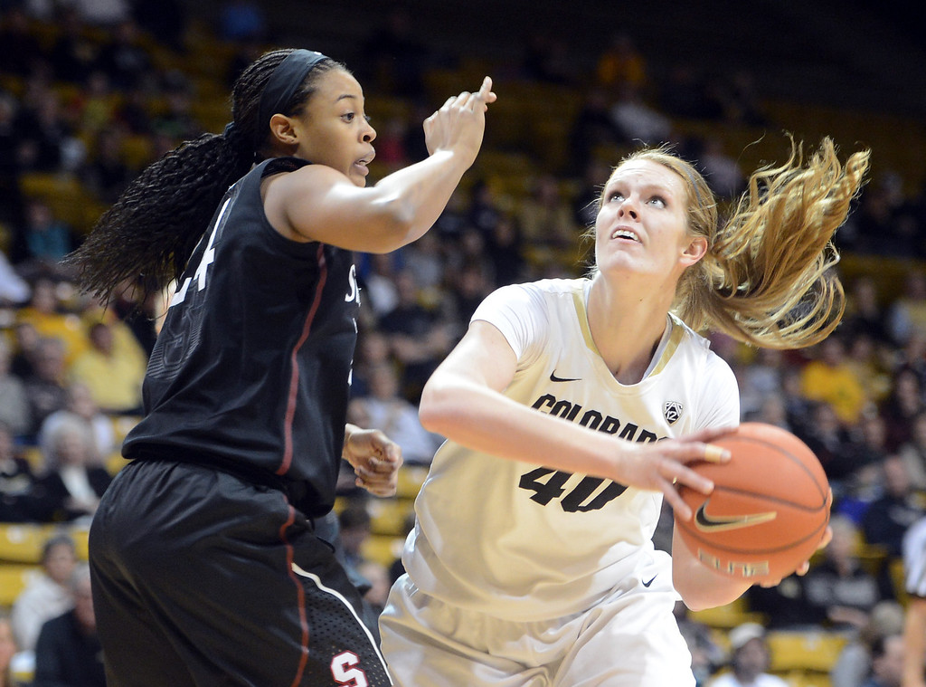 . Rachel Hargis of CU turns to shoot on Erica McCall of Stanford during the first half of the January 12, 2014 game in Boulder. Cliff Grassmick/Daily Camera