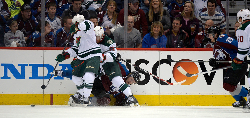 . Colorado Avalanche left wing Gabriel Landeskog (92) gets crushed against the boards by Minnesota Wild center Stephane Veilleux (19) and Minnesota Wild defenseman Jared Spurgeon (46) during the second period.   (Photo by John Leyba/The Denver Post)