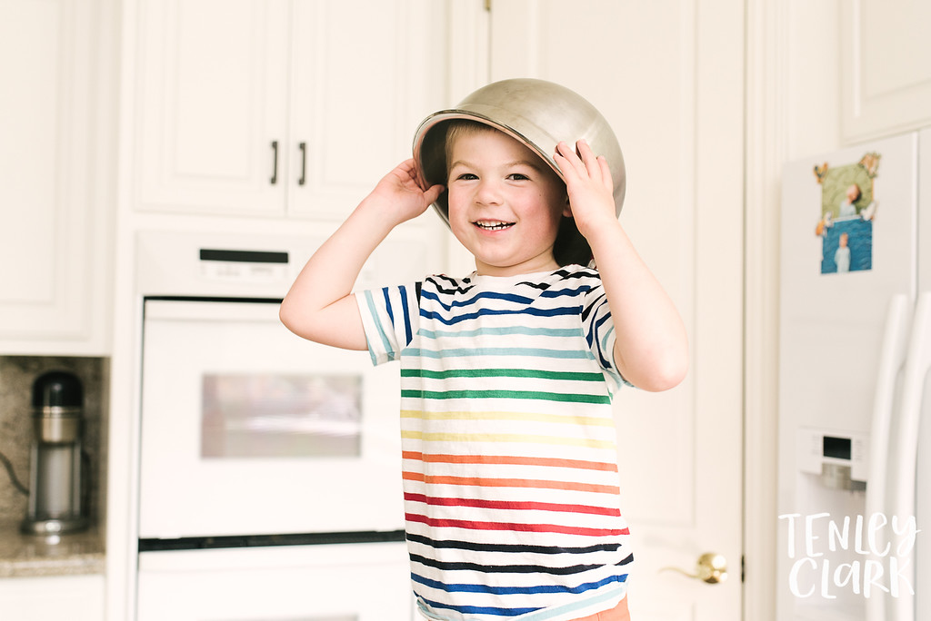 Mixing bowl on kid's head. Lifestyle in-home family photoshoot with snuggles, couch forts, baking, guitar, baseball, and playing cards. By Tenley Clark Photography.