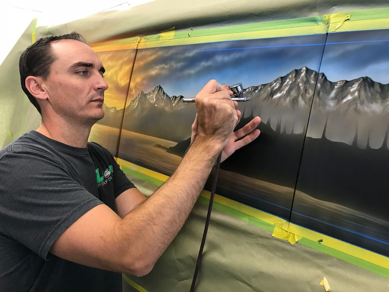 Dale starting a mural on a van.